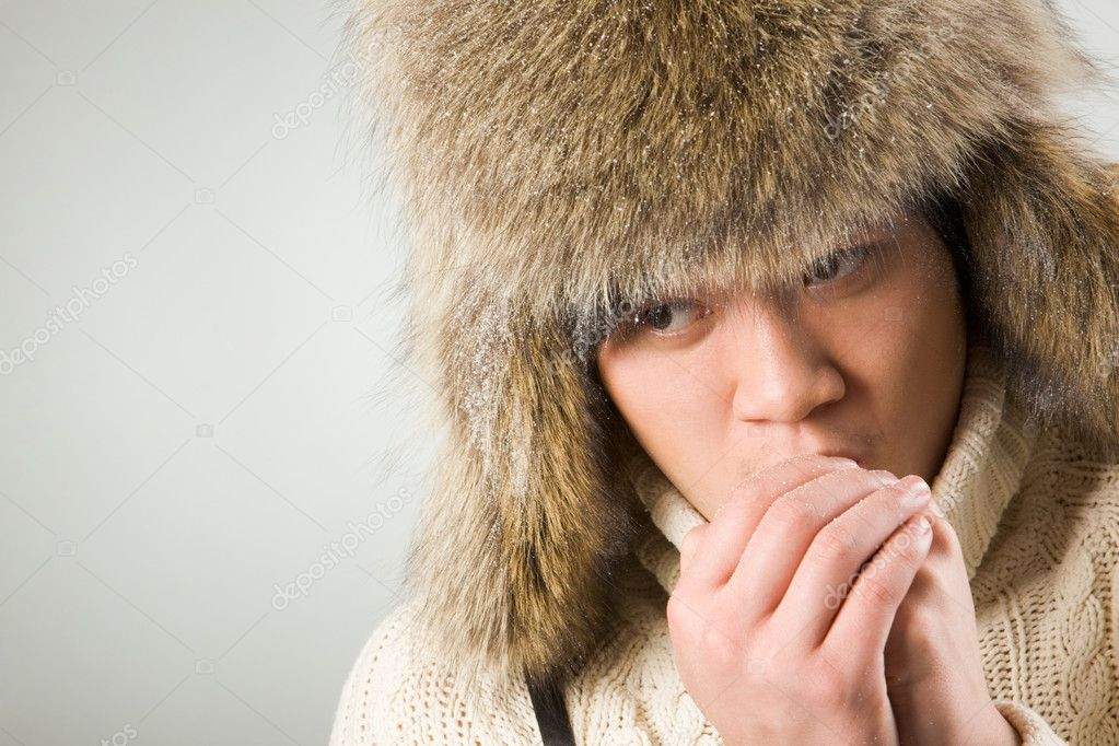 Portrait of cold man in fur hat and knitted sweater warming up his hands — Stock Photo #11148999