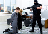 Image of two office workers standing on their knees in front of evil robber pointing gun at them — Stock Photo