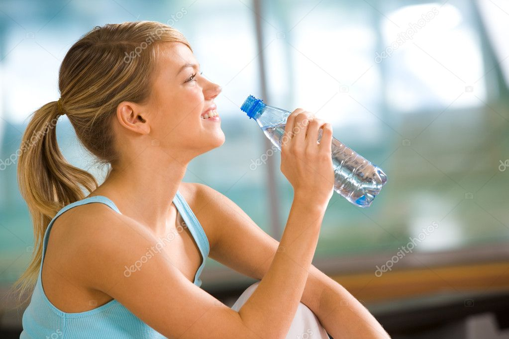 Profile of beautiful woman going to drink some water from plastic bottle after workout — Stock Photo #11215216