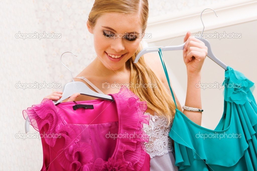 Image of pretty female looking at smart dresses while choosing a right one — Stock Photo #11216888