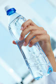 Bottle in hand — Stock Photo