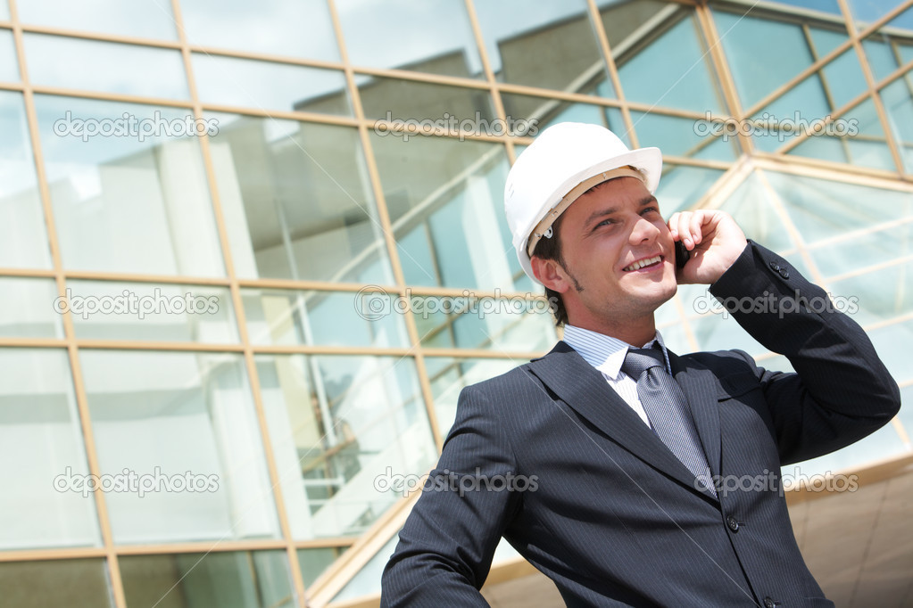 Portrait of confident foreman in helmet calling by mobile phone — Stock Photo #11242429