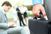 Hand with briefcase — Stock Photo