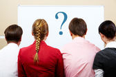 Rear view of business team with whiteboard in front of them — Stock Photo