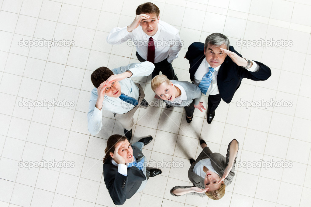 Portrait of confused business group standing on the floor and looking at camera — Stock Photo #11310136