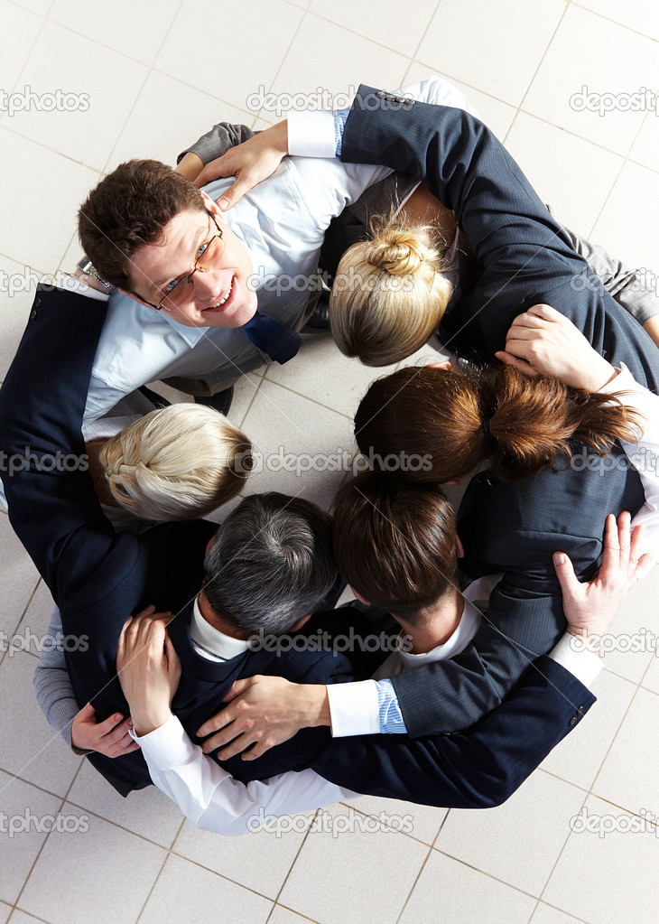 Above view of several business partners embracing each other while making circle with one of them looking at camera — Stock Photo #11310800