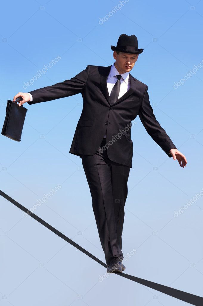 Photo of skilled businessman walking down ribbon or rope with blue sky at background  Stock Photo #11311748
