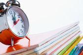 Alarm clock on copybooks — Stock Photo