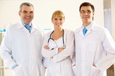 Portrait of friendly therapists standing in line and looking at camera with smiles — Stock Photo