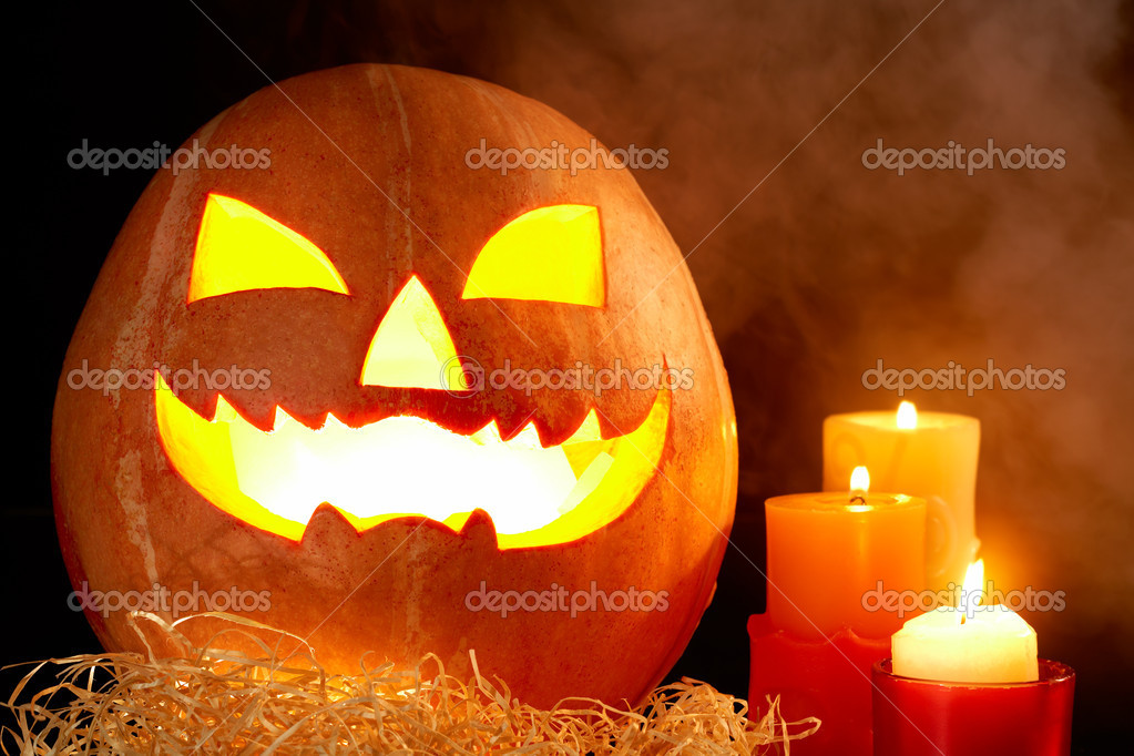 Image of big pumpkin with burning candle inside and three candles near by — Stock Photo #11337371