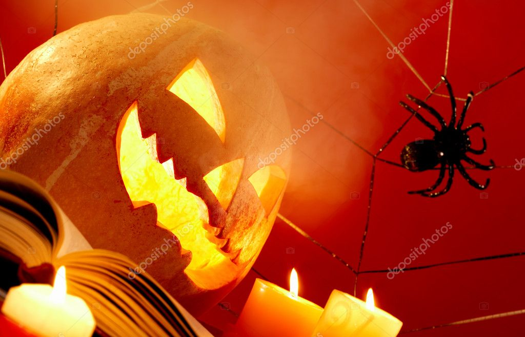 Image of Halloween pumpkin with burning candles and cobweb with spider near by  Stock Photo #11337382