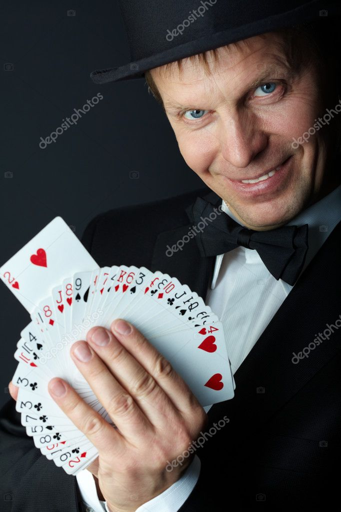 Image of male magician with cards looking at camera on black background — Stock Photo #11337624