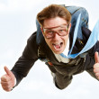 Conceptual image of happy man flying with parachute and showing thumbs up — Stock Photo #11340672