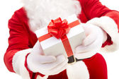 Photo of Santa Claus hands holding giftbox with red bow — Stock Photo
