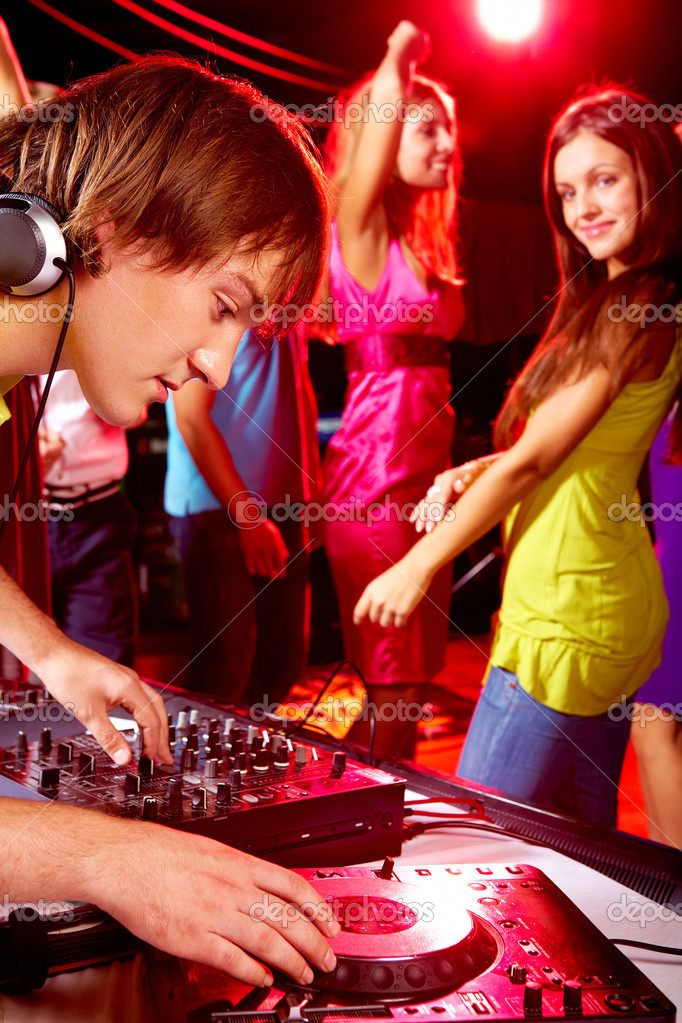 Smart deejay adjusting technics with dancing girls on background — Stock Photo #11341073