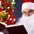 Santa reading a book — Stock Photo #11582540