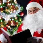 Santa reading a book — Stock Photo