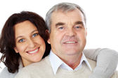 Portrait of happy mature couple looking at camera while woman embracing man — Stock Photo