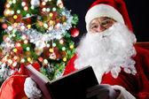 Santa lezen van een boek — Stockfoto