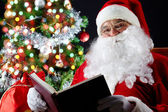 Santa reading a book — Stockfoto