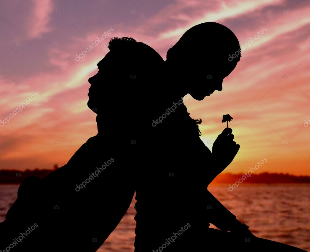 Silhouette of couple sitting back to back on background of sunset — Stock Photo #11582191