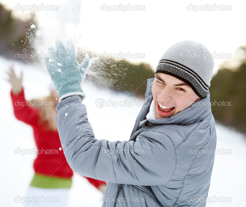 Image of attractive young man laughing while under snowball bombing  Stock Photo #11582303