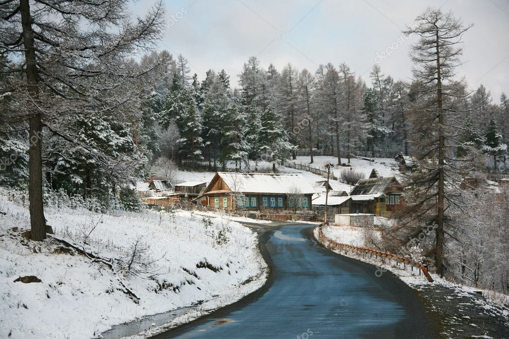 View of country road in winter with snow-covered wooden huts and trees on both sides  Stock Photo #11583732
