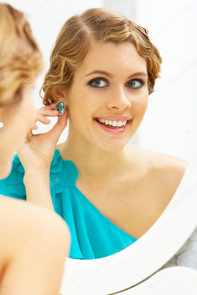 Image of pretty female looking in mirror and putting on earrings  Stock Photo #11627476