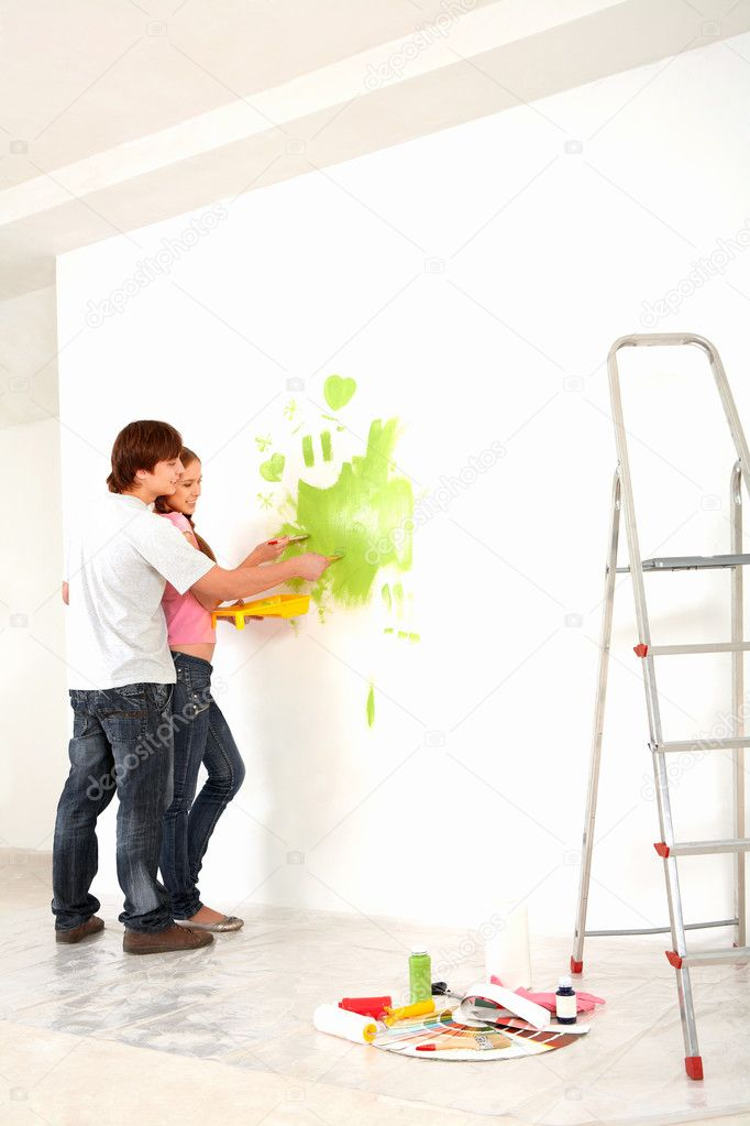 Affectionate couple helping each other to paint walls in new house — Stock Photo #11628389