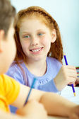 Portrait of smart schoolgirl looking at classmate at drawing lesson — Stock Photo