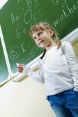 Girl by blackboard — Stock Photo
