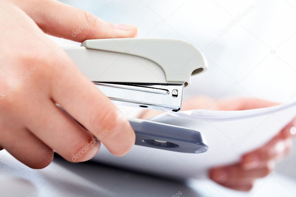 Close-up of female hand stapling the documents  Stock Photo #11630197