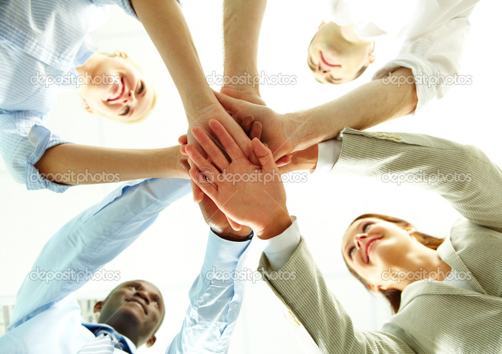 Four business putting their hands on hands of their colleagues  Stock Photo #11632334