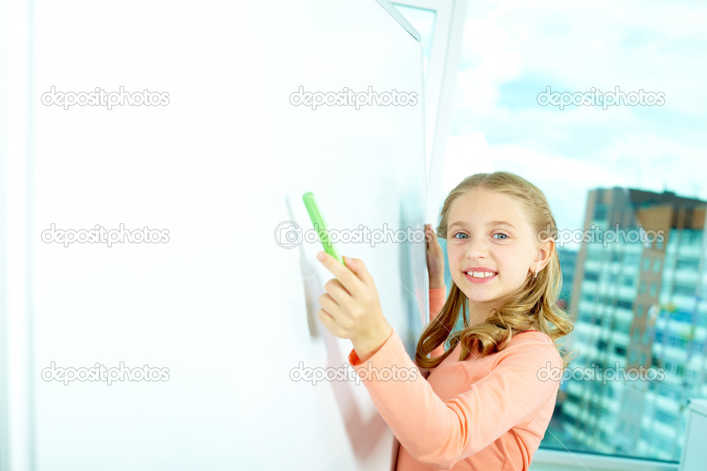 Portrait of smart schoolgirl pointing at whiteboard and looking at camera — Stock Photo #11633547
