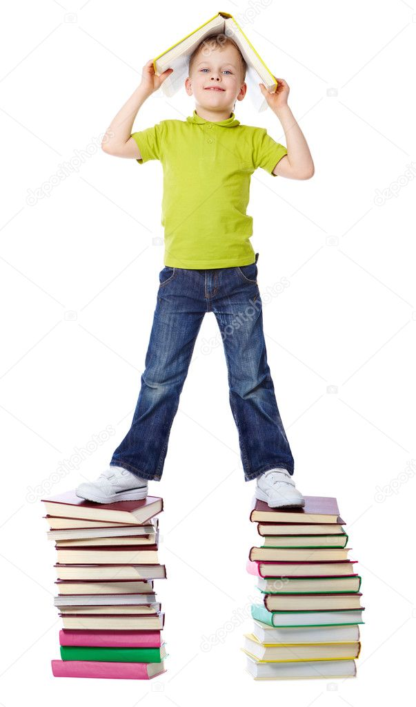 A cheerful boy standing on two heaps of books and holding a book over his head — Stock Photo #11634769