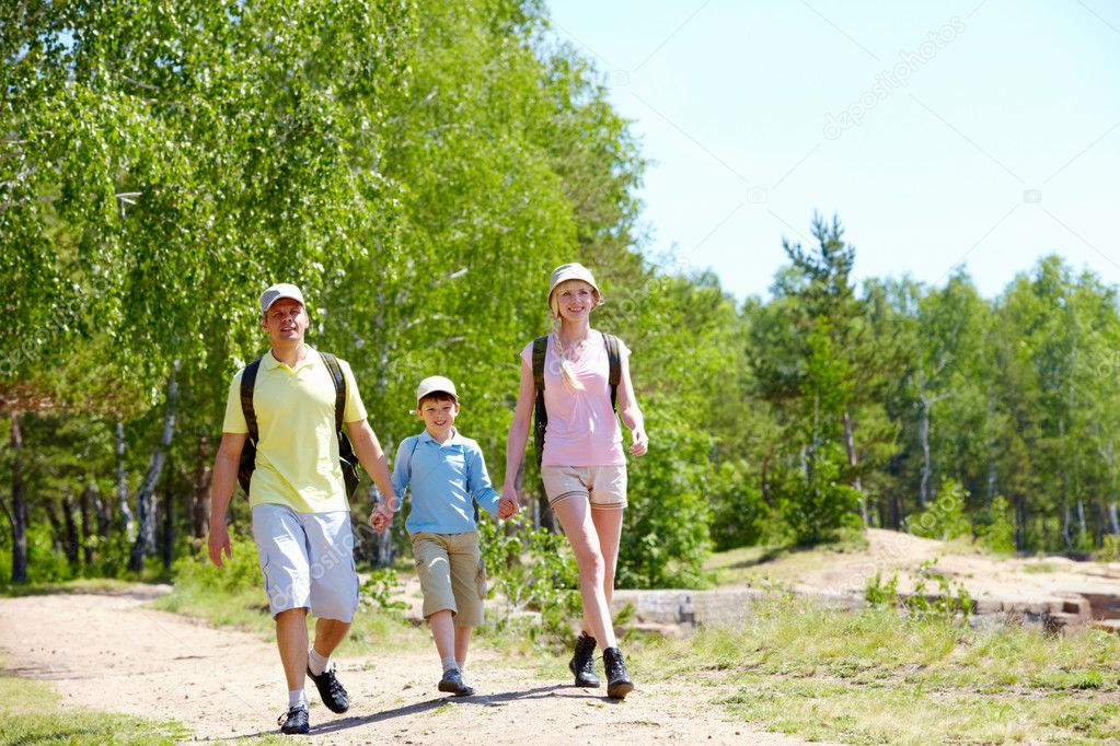 Portrait of three family members walking down road at summer — Stock Photo #11634984