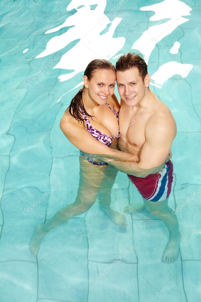 Photo of happy couple in swimming pool embracing and looking at camera — Stock Photo #11635023