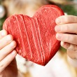 Close-up of red wooden heart in child's hands showing it — Stock Photo