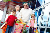 Portrait of happy grandparents and grandchildren with package of food near supermarket — Stock Photo