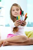 Girl giving crayons — Stock Photo