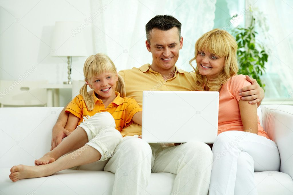 Image of friendly family sitting on the sofa and looking at laptop — Stock Photo #11662159