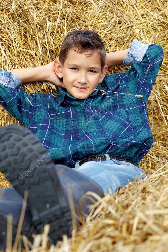 Handsome lad lying on hay in countryside — Stock Photo #11662743