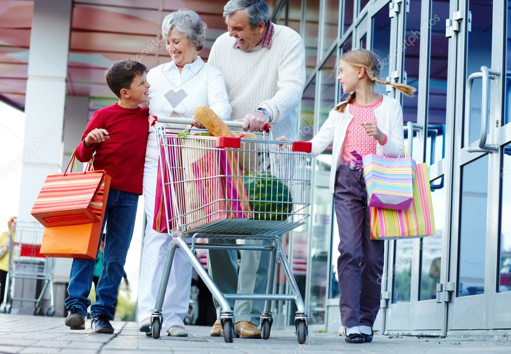 Portrait of happy grandparents and grandchildren walking and chatting after shopping — Stock Photo #11662826
