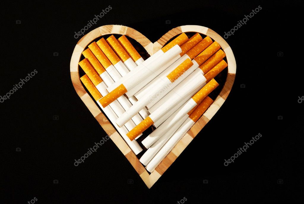 Cigarettes in heart shape against black background — Stock Photo #11664351