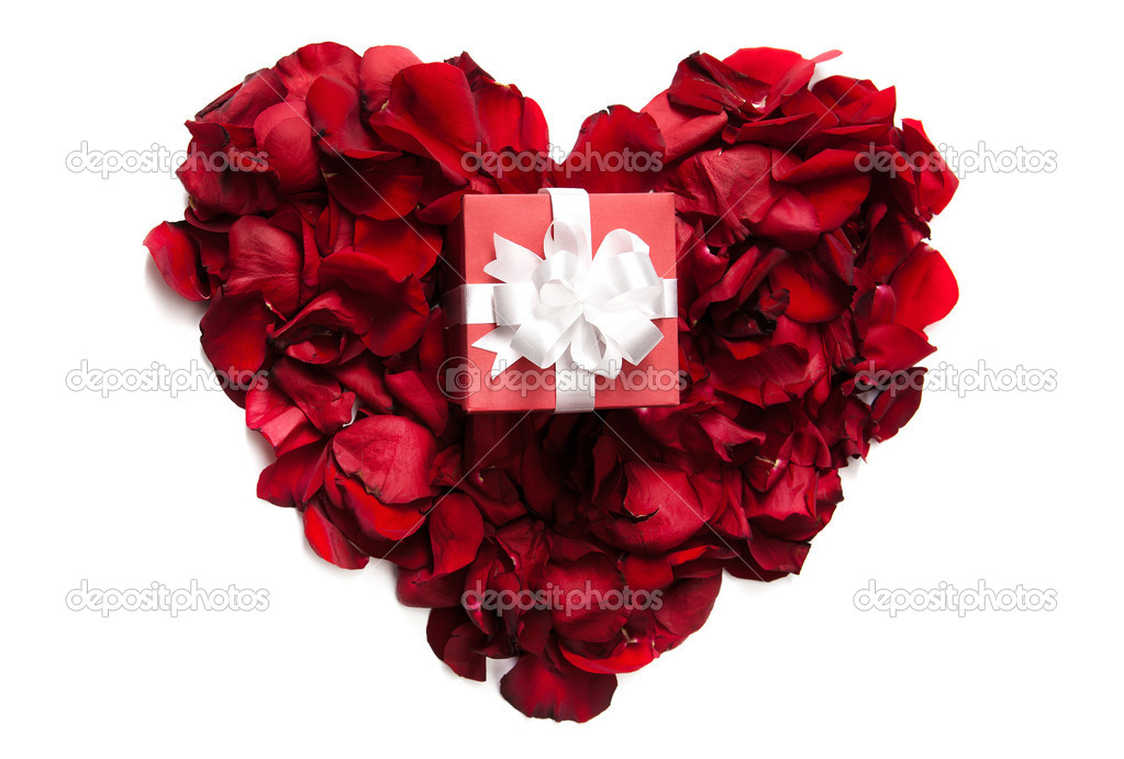 Red rose petals making up heart with small giftbox on it  Stock Photo #11664417