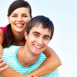 A young man carrying a woman on back — Stock Photo