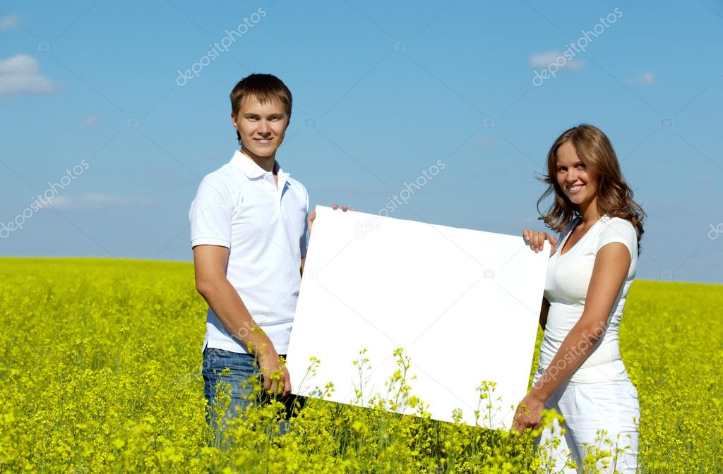 Portrait of happy young couple with blank paper standing in meadow — Stock Photo #11670761