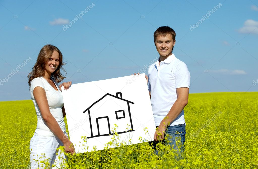 Portrait of happy young couple showing house drwan on paper in meadow — Stock Photo #11670762
