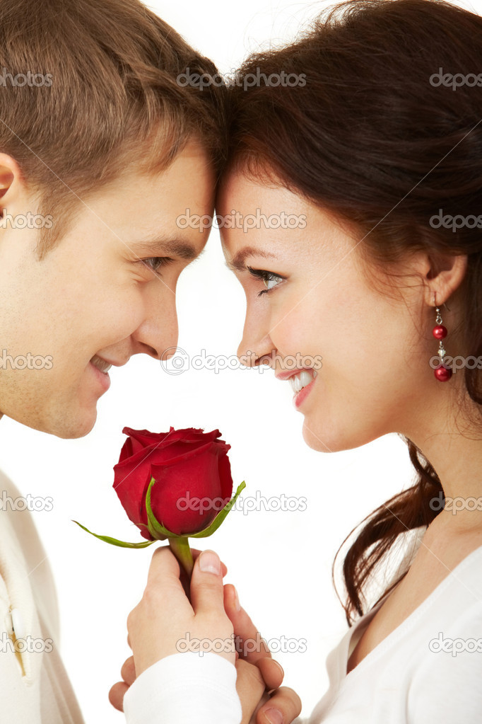 Close-up of two young looking at each other and holding a rose — Stock Photo #11671481