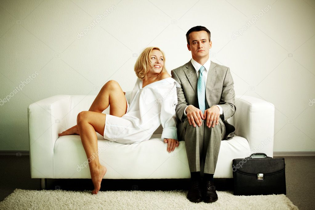 Photo of serious man sitting on sofa with happy seductive woman looking at him — Stock Photo #11672018